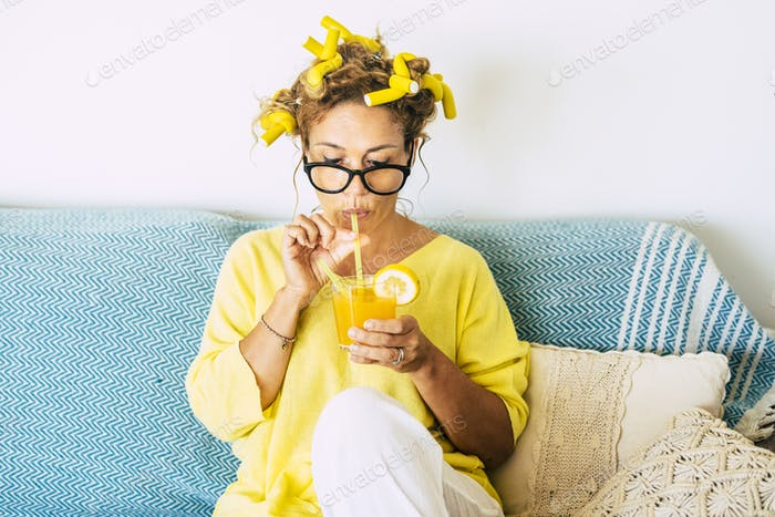 Yellow colors portrait of beautiful caucasian young adult woman drinking healthy orange juice