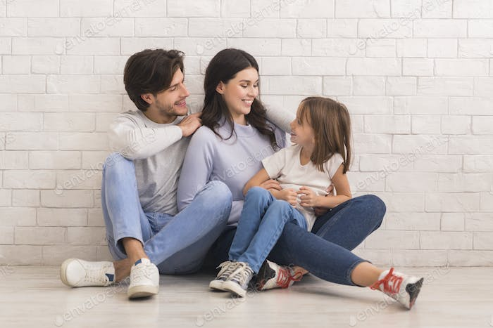 Affectionate Young Family Bonding Together While Sitting On Floor At Home