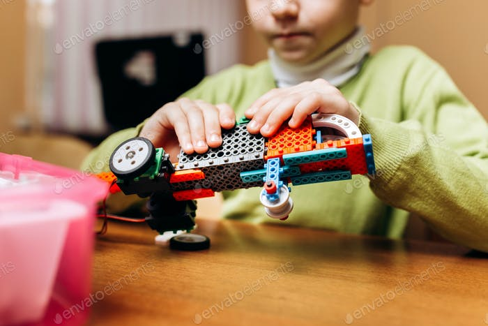 Focused boy dressed in green sweater sits at the table in the robotics school and makes a robot from