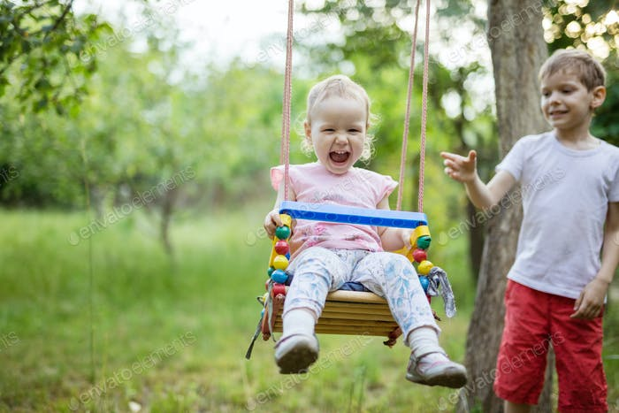 Young boy pushing toddler sister on swing