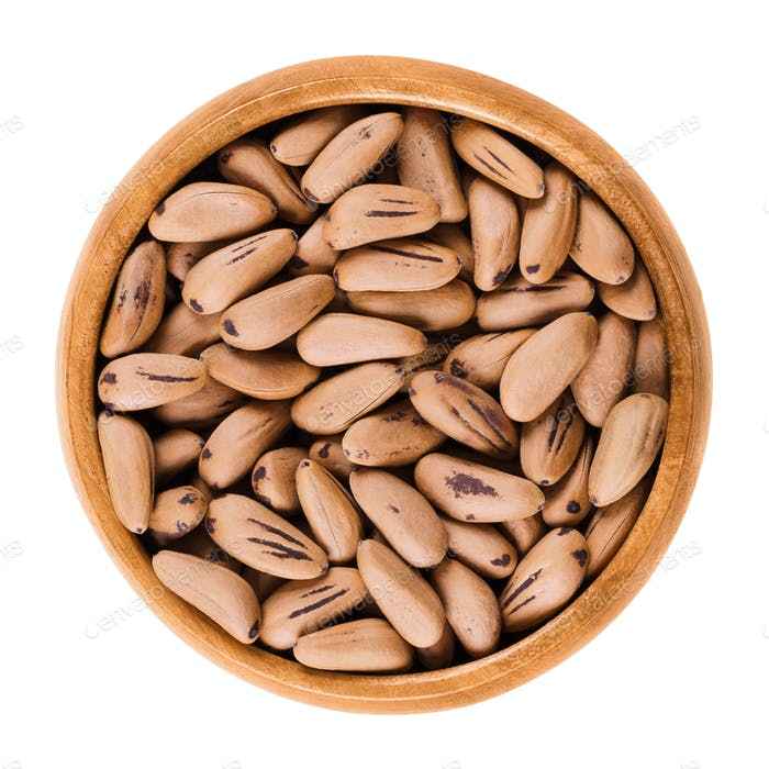 Stone pine seeds in wooden bowl over white