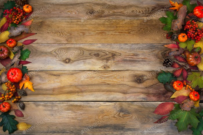 Fall background with leaves and cones on old table