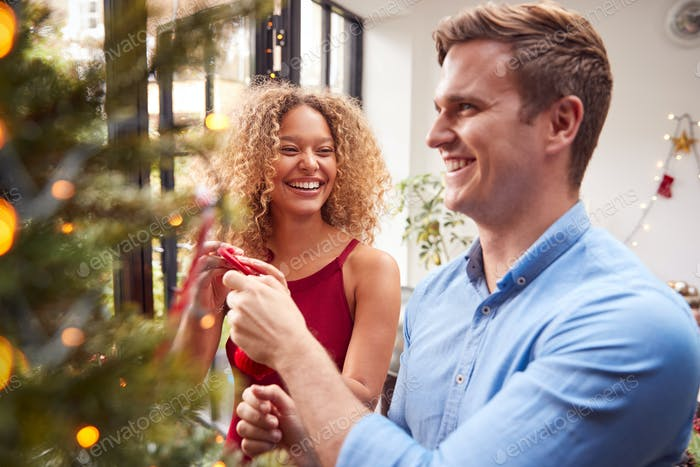 Couple At Home Hanging Decorations On Christmas Tree Together