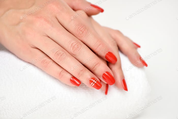 Manicure - Beautiful manicured woman's nails with red nail polis
