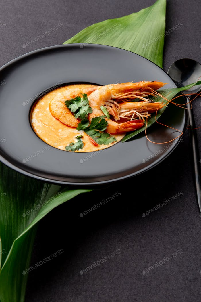 Seafood Soup decorated with whole shrimps and tropical leaves on black plate, black background.