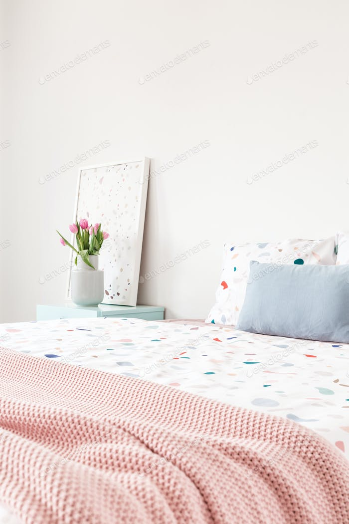 Pink blanket on bed with patterned sheets and blue cushion in be