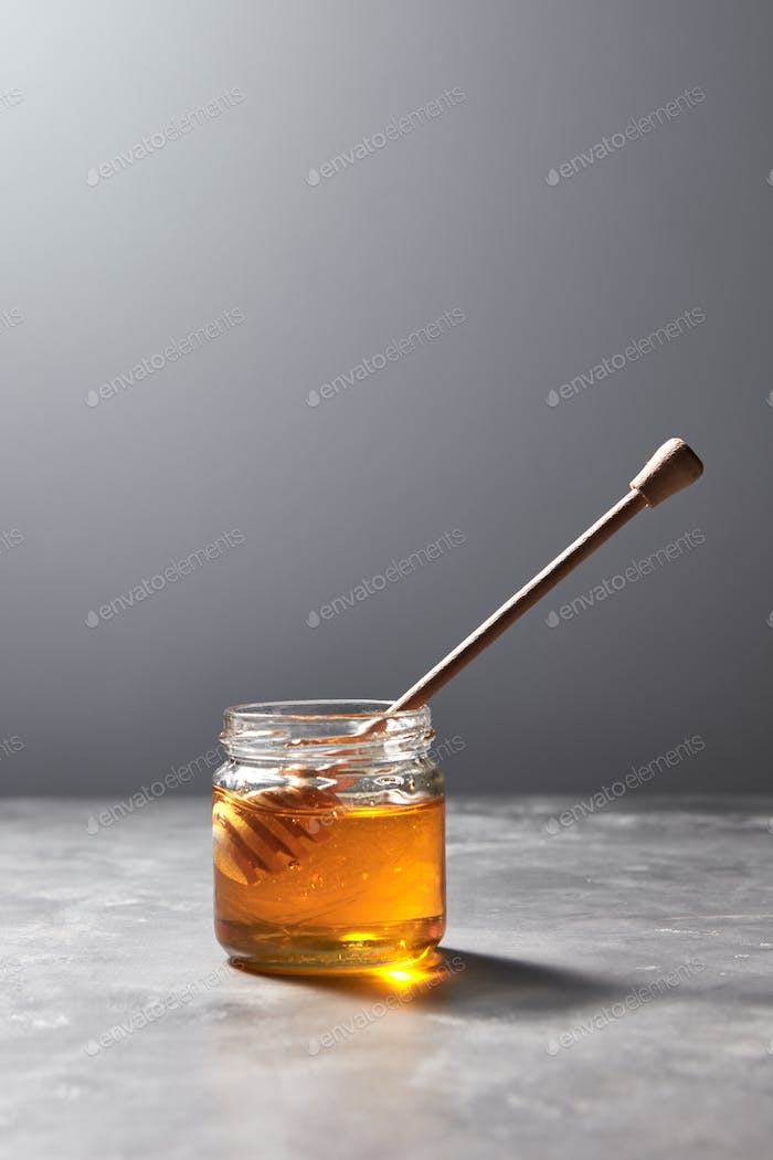 Aromatic fresh natural honey with dipper in a glass pot on a gray stone table, pure natural sweet