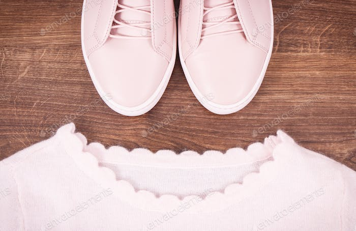 Womanly leather shoes and sweater on boards
