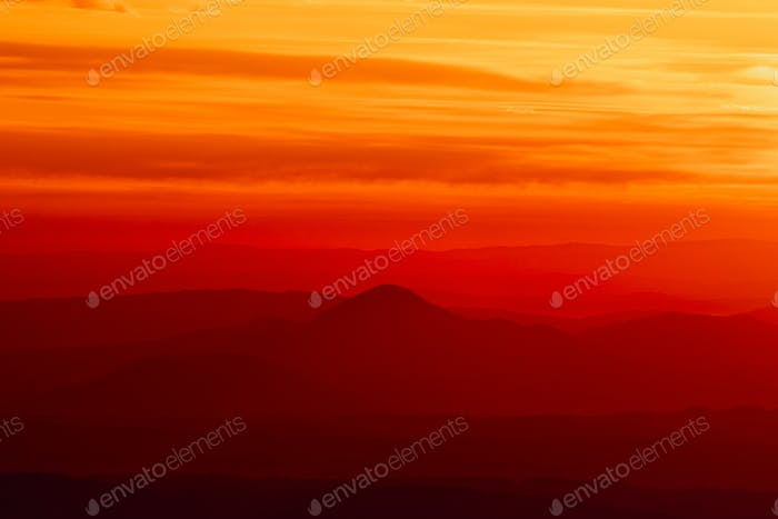 Tranquil landscape of layered mountains silhouettes during colorful sunrise, Slovakia