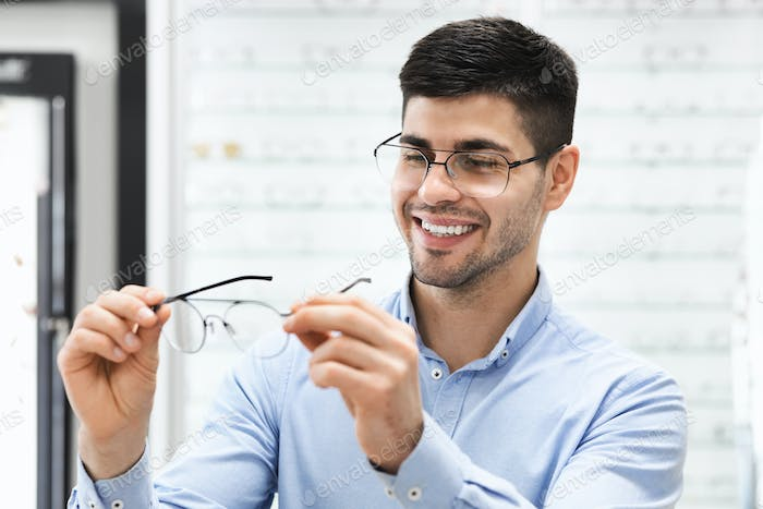 Portrait of handsome young guy choosing spectacles