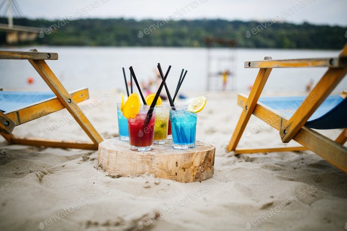 Exotic summer drinks , blur sandy beach on background