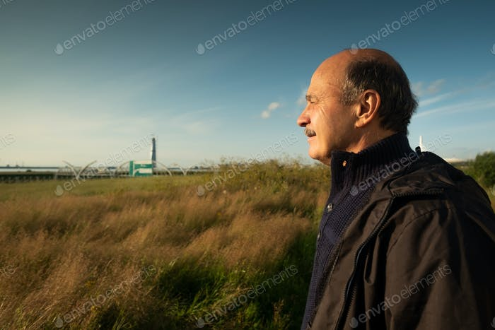 Portrait of senior man looking aside while walking outdoor