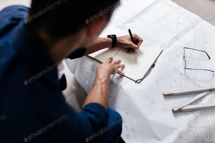 Professional architect makes notes in a notebook on a table with a drawing and ruler