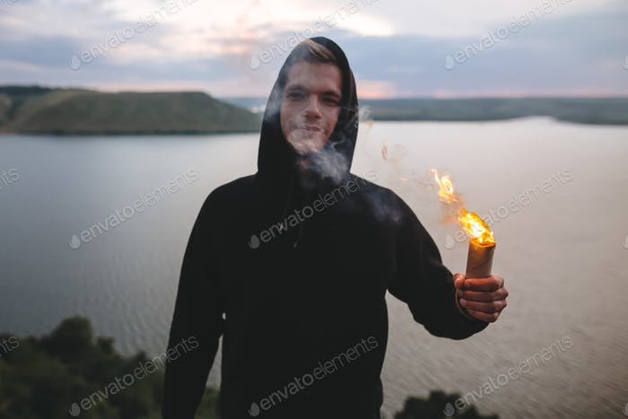 Ultras hooligan holding sparkler with burning fire in hand while standing on top of rock mountain
