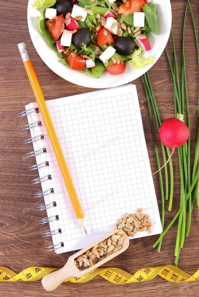 Fresh greek salad with vegetables, centimeter and notepad for writing notes