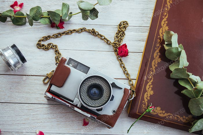 Retro-Kamerolle Fotofilm und Blumen auf weißem Holzhintergrund