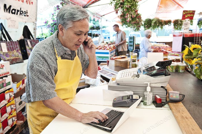 Man wearing apron standing at the checkout of a food and vegetable market, on the phone, typing on