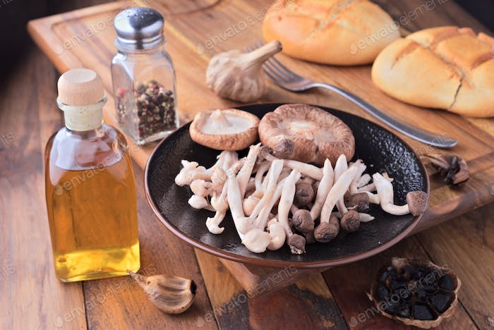 various types of raw edible mushrooms on classic wooden board