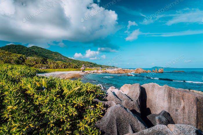Picturesque tropical coastline with hidden beach with unique big granite rocks, lush foliage and