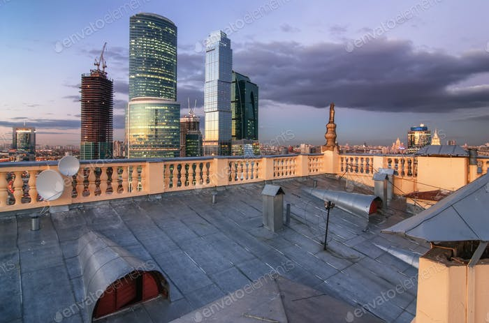 Roof of the old building with balustrades around the perimeter on the background of skyscrapers