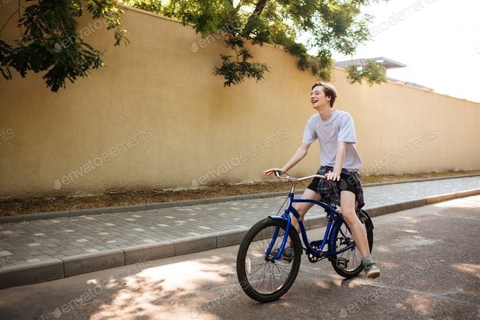 Portrait of smiling boy joyfully riding bicycle