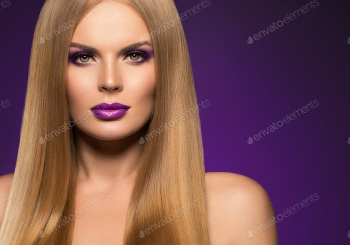 Color make up woman with long hair blond color purple background. Monochrome.