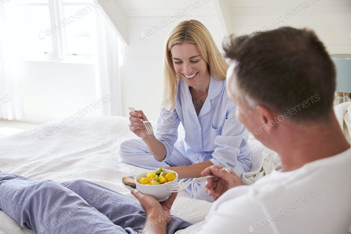 Couple Wearing Pajamas Sitting In Bed Eating Breakfast Together
