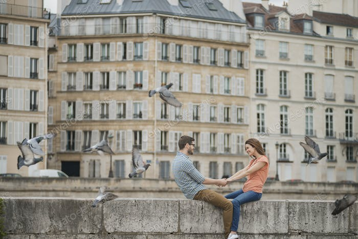A couple, man and woman sitting on the parapet of a bridge over the River Seine.