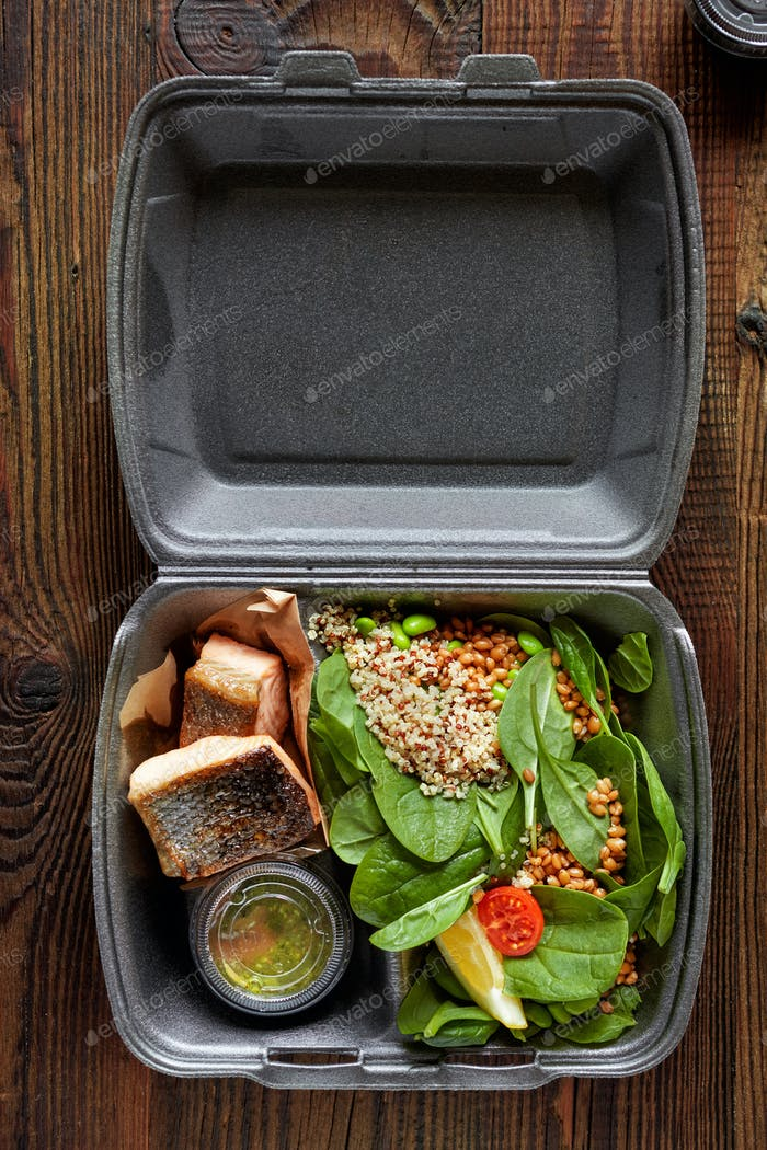 fried salmon pieces and spinach salad in plastic box