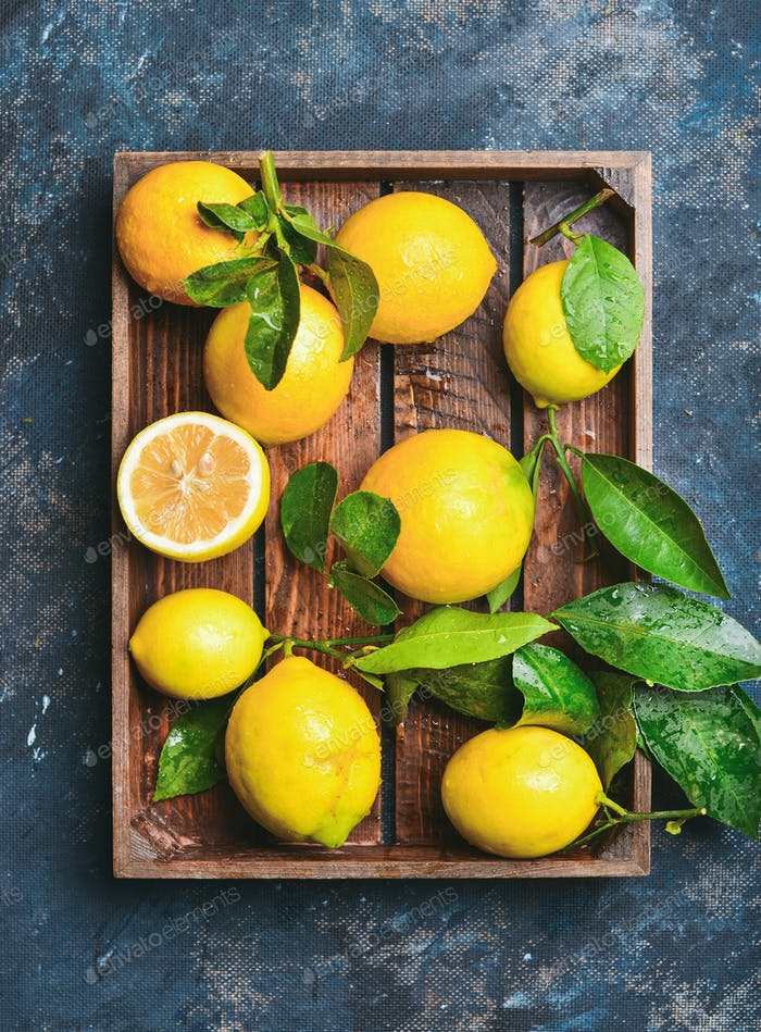 Freshly picked lemons with leaves in rustic wooden tray