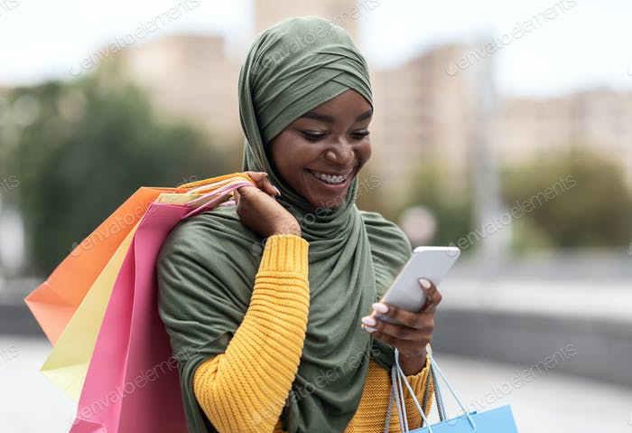 Taxi App. Black Muslim Woman Ordering Cab Outdoors Via Application On Smartphone
