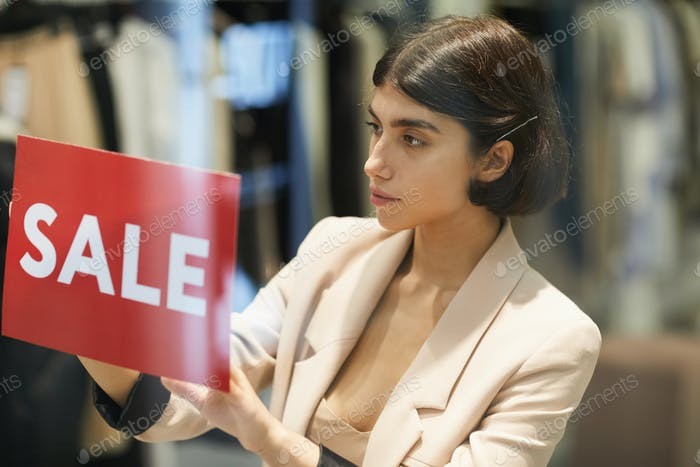 Woman Hanging Sale Sign in Store
