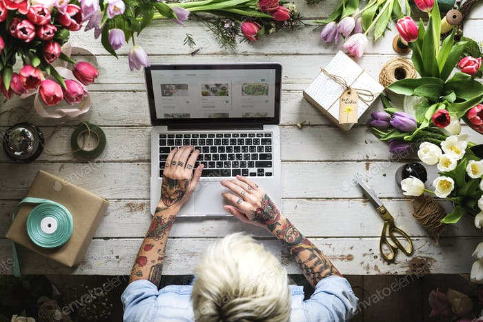 Woman Using Laptop Searching on Internet to Shop Flowers Plants
