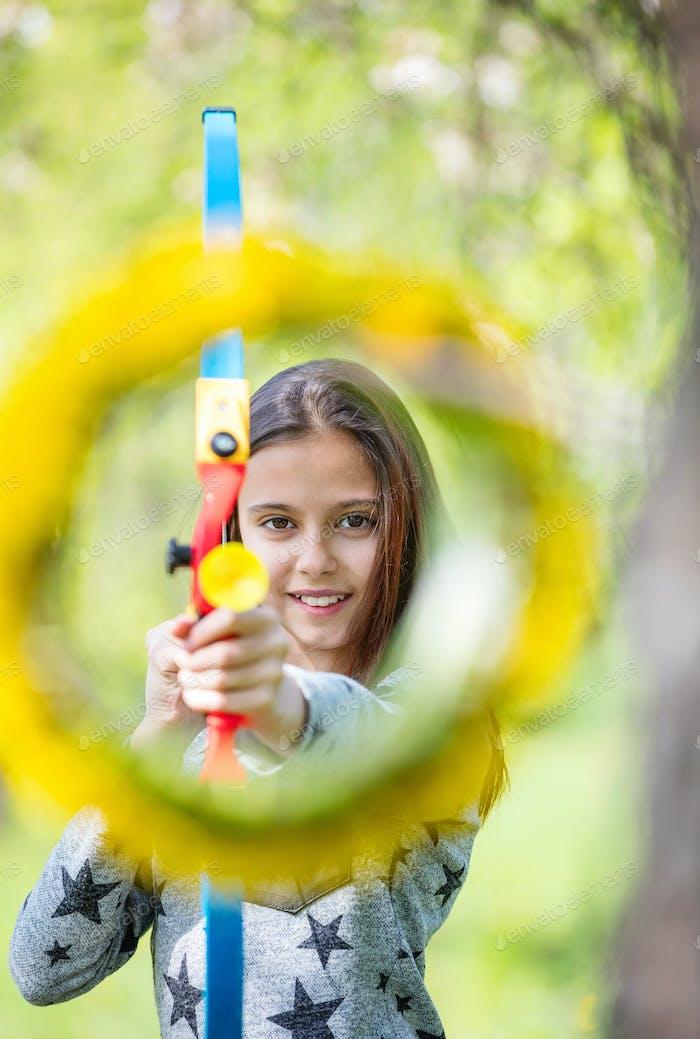 Junges Mädchen Bogenschütze mit Bogen Ziel durch Blumenkranz