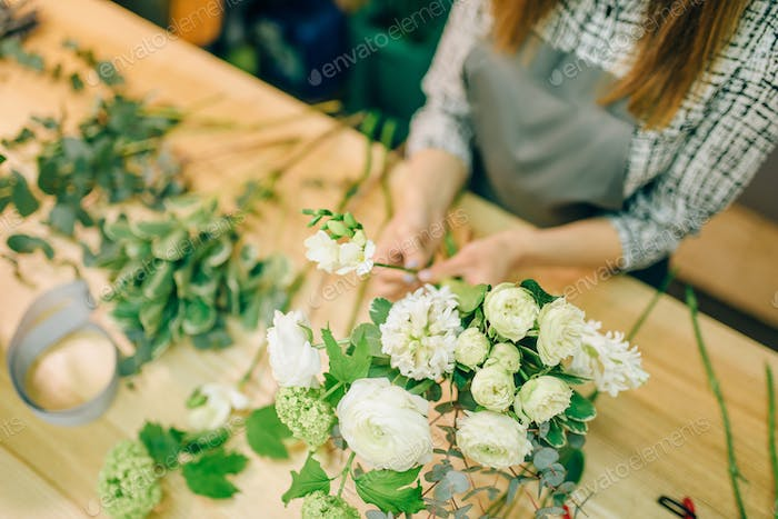 Female florist with pruner in hands makes bouquet