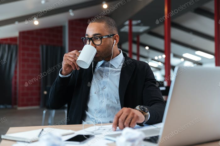 Businessman drinking and listening to music