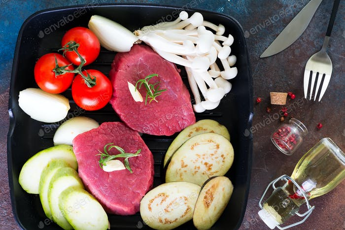 Raw beef steak on the bone with fresh vegetables in a pan on a dark stone background, top view