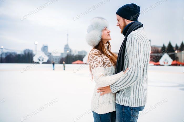 Love couple hugs on skate rink