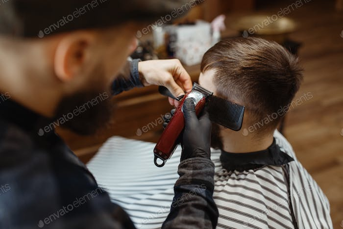 Barber in hat cuts the client 's hair, barbershop