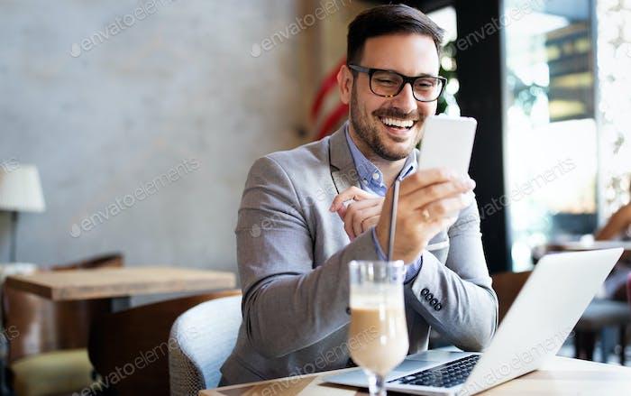 Porträt von Geschäftsmann arbeiten, im Gespräch auf Mobiltelefon im Büro