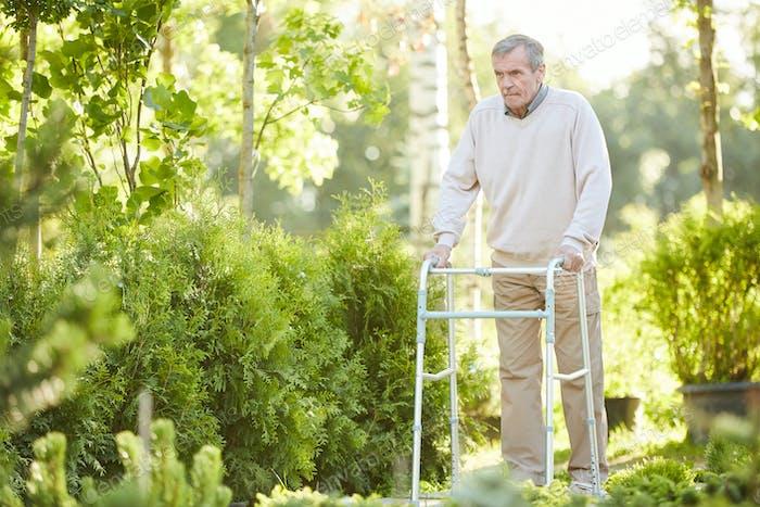 Senior Hombre Uso andador en Parque