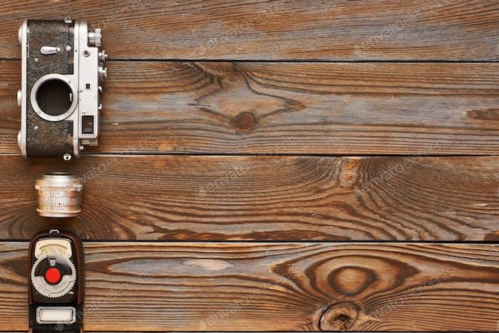 Vintage-Kamera und Objektiv auf Holzhintergrund