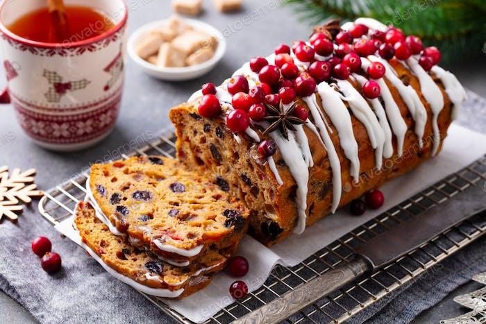 Christmas fruit cake, loaf bread on cooling rack with mug tea. Grey background. Close up