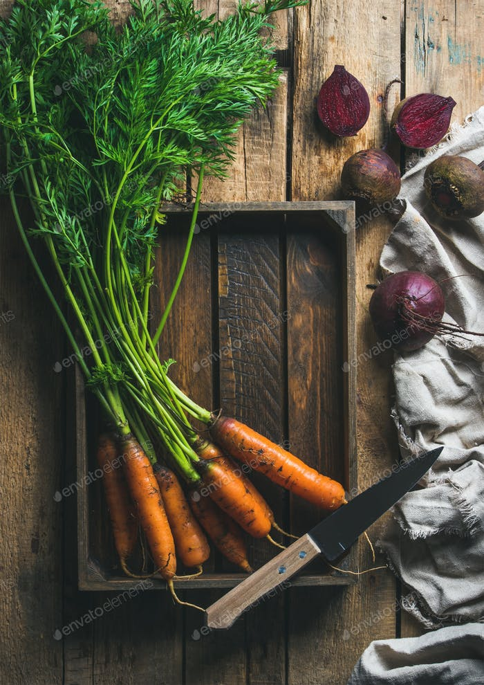 Garden carrots and beetroots in wooden tray over rustic background