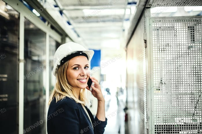 A portrait of an industrial woman engineer on the phone, standing in a factory.