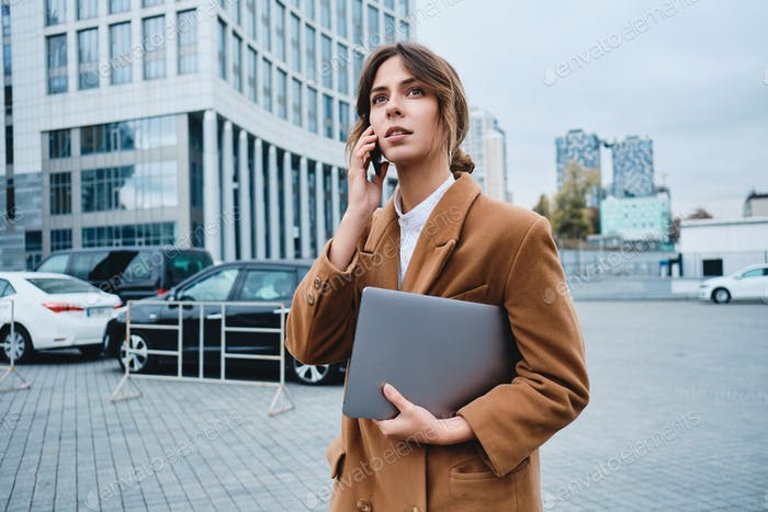 Young pensive businesswoman in coat with laptop looking away talking on cellphone on city street