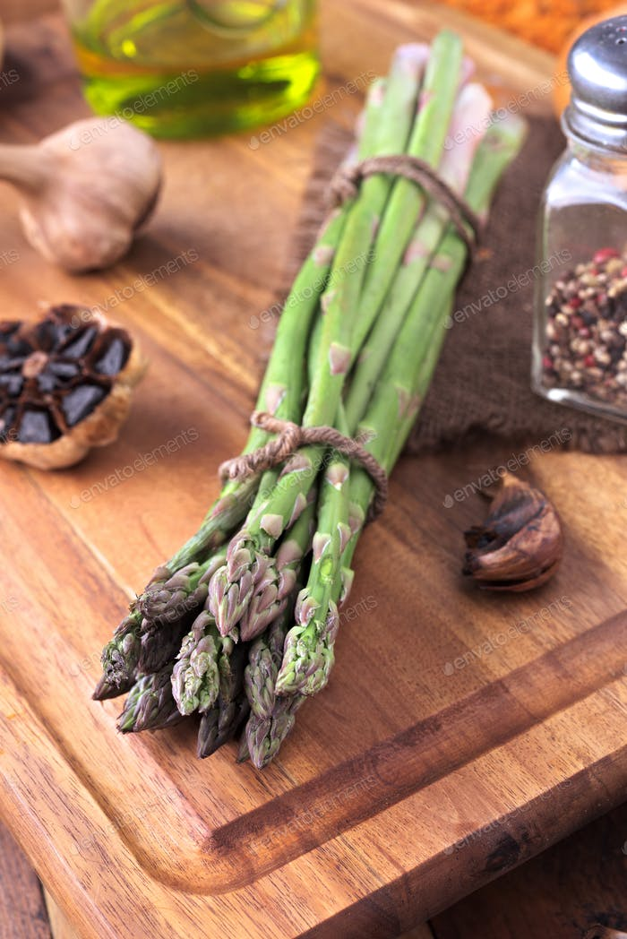 bunch of green tied and raw asparagus on classic wooden board