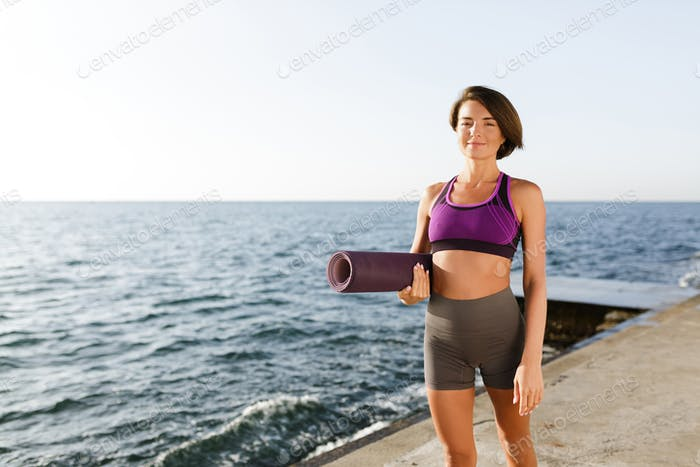 Young smiling woman with dark short hair holding yoga mat in hand while walking by the sea