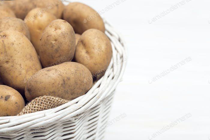 Potatoes in basket on wooden white background
