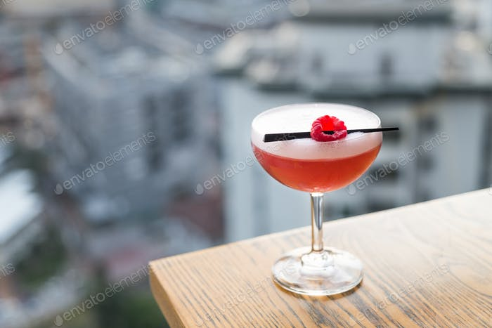 Red cocktail with cherry on table top